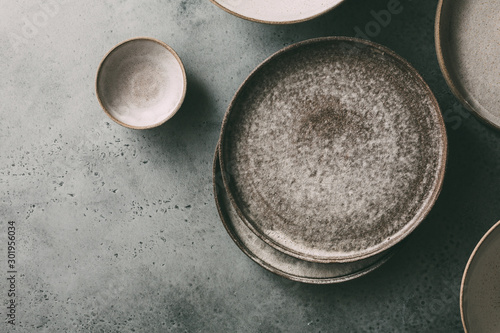 Empty ceramic bowls and plates on a dark background. Top view, copy space.