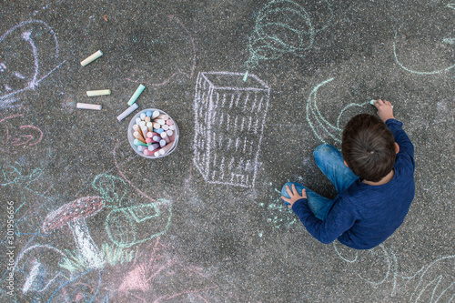 Leinwand Poster Young boy drawing on the sidewalk with chalk