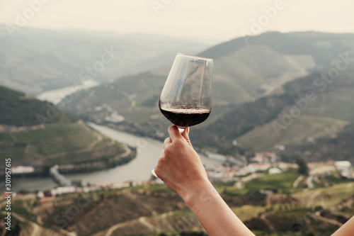 Spoed Fotobehang Zalm hand holding a glass of red wine on background Landscape of Douro Valley, Portugal. Port Wine production place