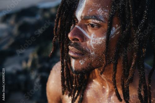 Obraz Outdoor emotional Fashion Portrait of African man wearing long dreadlocks and fancy makeup white face paint - fototapety do salonu