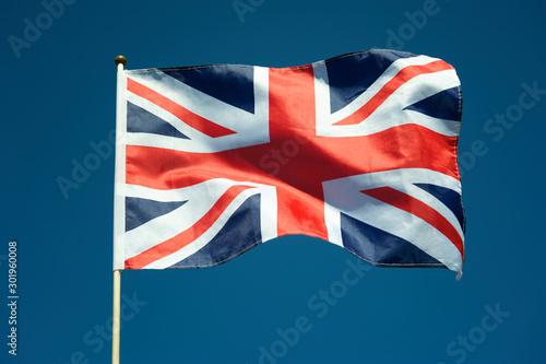 Photo Single British Union Jack flag flying on a flag pole in sunny bright blue sky