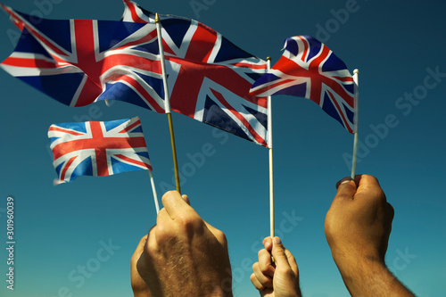 Obraz Group of patriotic hands waving Union Jack British flags in bright blue sky at a Brexit protest in London - fototapety do salonu