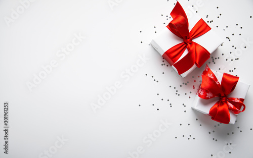 Fototapeta White gifts with red ribbon, present on white background top view. Merry Christmas and Happy Holidays. New Year. Valentine's day. Birthday. obraz na płótnie