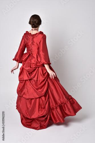 Fotografía full length portrait of a brunette girl wearing a red silk victorian gown