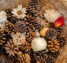 Closeup Of Open Pine Cones And Flowers In A Wicker Basket, Photographed From Above.