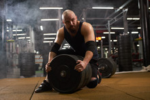 Young Man With Bald Head, Dressed In Black Stylish Sportswear Looks Aside With Interest, Sitting On Barbell, Changing Metal Weight Plate, Gym Atmosphere, Indoor Shot