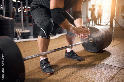 plakat Side shot of strong young bodybuilder preparing to lift heavy barbell in modern gym hall, hands in talc, getting ready for weight lifting training, active people concept