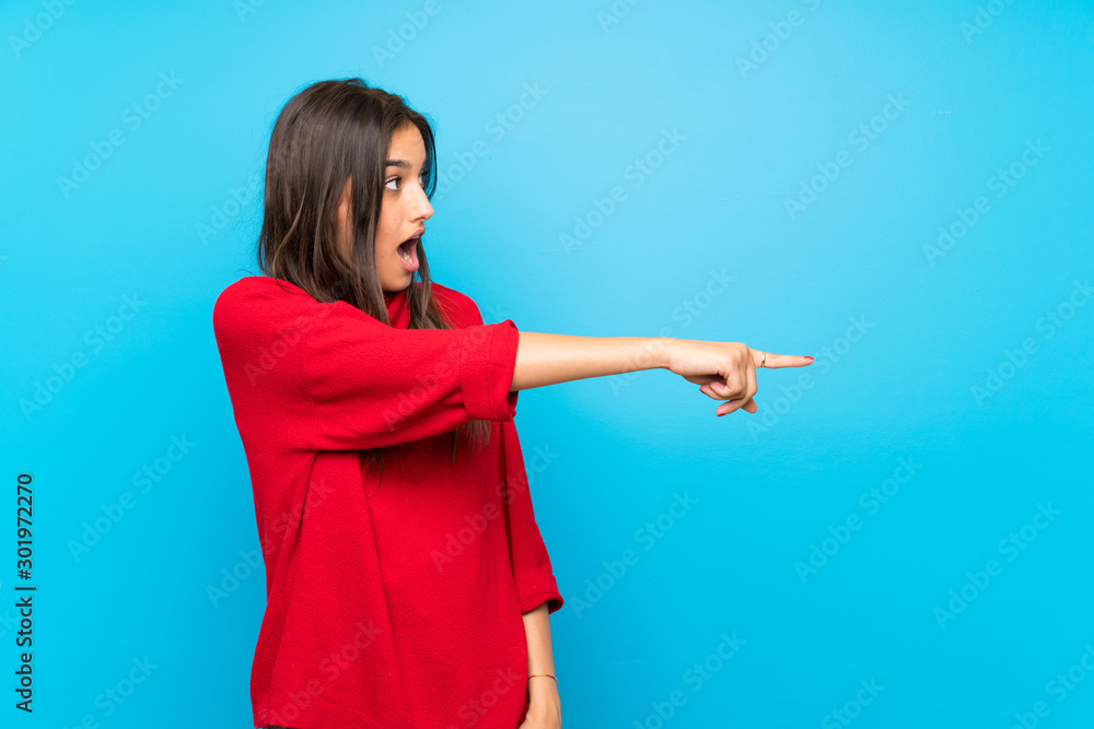 Fototapety, obrazy: Young woman with red sweater over isolated blue background pointing finger to the side