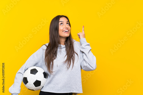 Young football player woman over isolated yellow background intending to realize Fototapet