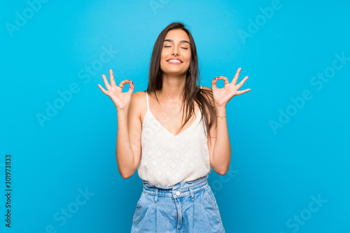 Young woman over isolated blue background in zen pose Canvas-taulu