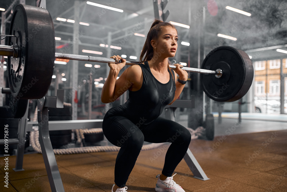 Fototapeta Charming strong female powerlifter dressed in black sportswear and white sneakers, doing squats, trying to stand with heavy barbell, professional sport concept, indoor shot