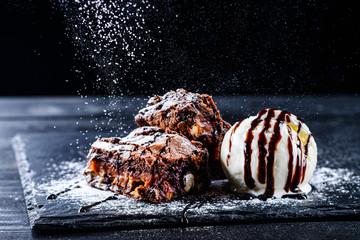 kuglica sladoleda od vruće čokolade u brownieju i kriška čokoladne torte