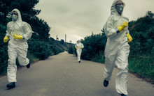 People With Bacteriological Protection Suits Running Away On A Lonely Road