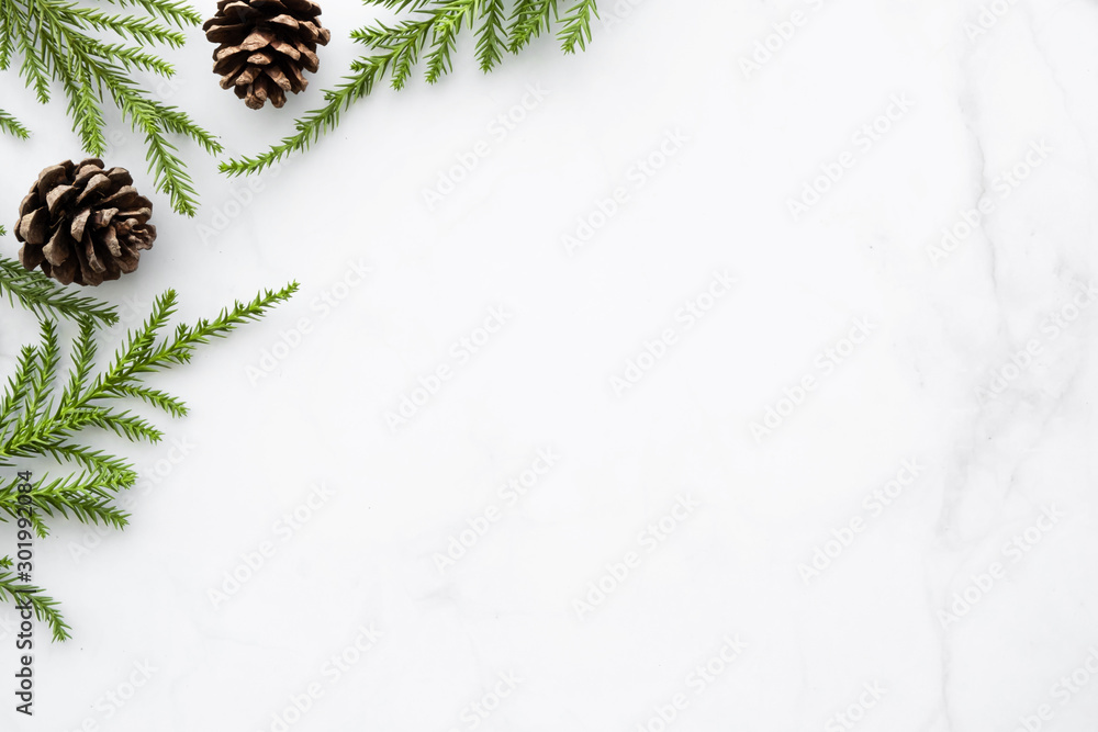 Fototapeta White marble table with Christmas decoration including pine branches and pine cones. Merry Christmas and happy new year concept. Top view with copy space, flat lay.