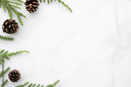 Fotografia  White marble table with Christmas decoration including pine branches and pine cones