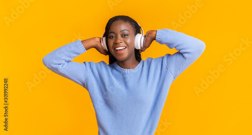 Emotional black girl with headset listening to music and singing - 301992248