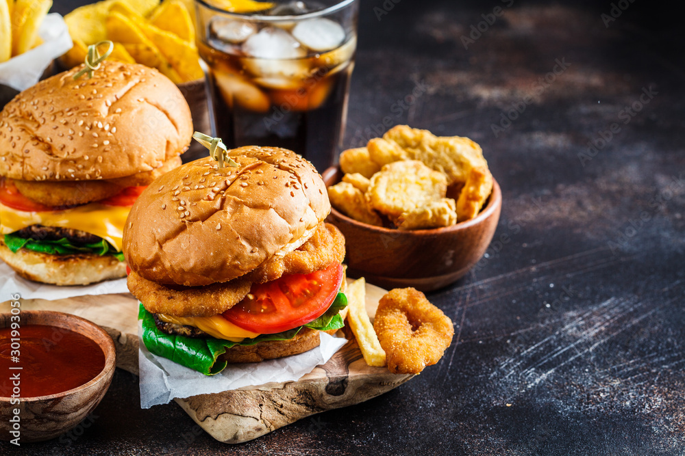 Fototapety, obrazy: Assortment of fast food. Junk food background. Cheeseburgers, french fries, nachos, donuts, soda and nuggets on dark background.