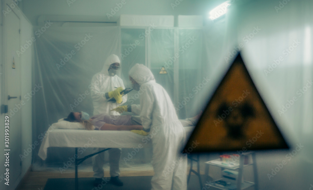 Fototapety, obrazy: Two people attending to a woman with a virus lying on a stretcher in a field hospital with bio hazard symbol in the foreground