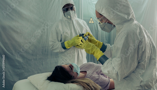 Fotografiet Two people attending to a woman with a virus lying on a stretcher in a field hos