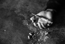 Addict Man Dead After Inject Drug Overdose With Syringe Injection Heroin To Hand. Narcotic Addiction Concept, International Day Against Drug Abuse. Black And White Picture