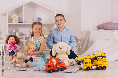 Obraz beautiful happy caucasian children sitting in their room, boy with car, girl  with doll - fototapety do salonu