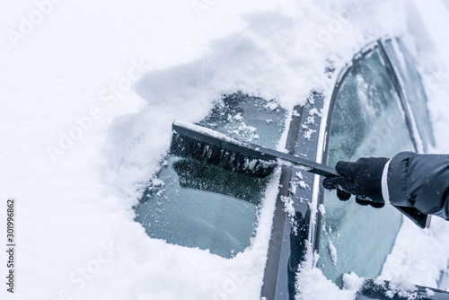 Hand are holding and brushing car window clean of snow. car covered in snow during heavy snow fall. Winter and seasonal concept.