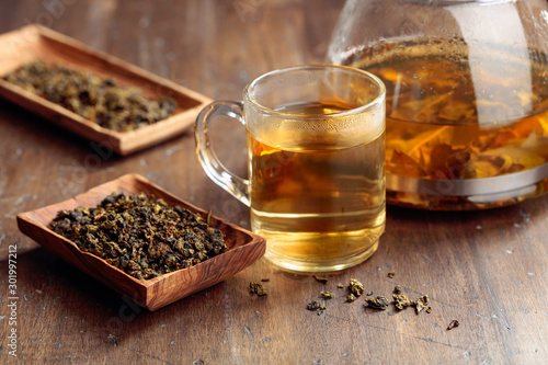 Recess Fitting Tea Hot green tea in glass mug. Dried tea leaves and hot drink on a wooden table.