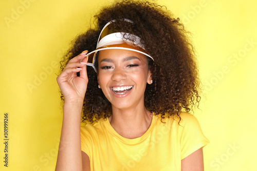 Fotografiet  Such a beautiful smile! Afro girl in yellow clothes on yellow background