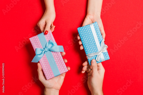 Fototapeta Top view of a woman and a man exchanging gifts on colorful background. Couple give presents to each other. Close up of making surprise for holiday concept obraz