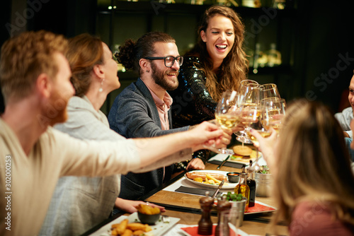 Best friends sitting in restaurant for dinner and making a toast with white wine. On table is food. - 302000253