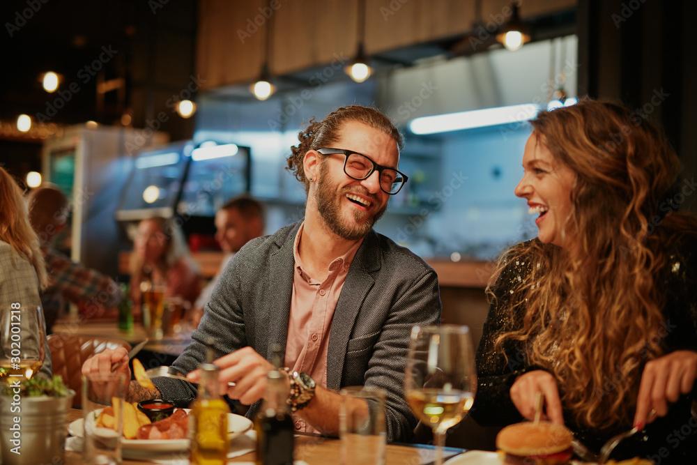 Fototapeta Best friends sitting in restaurant for dinner, drinking wine and chatting.