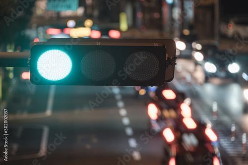 Obraz 夜の信号機と交通の様子, A Traffic Light and Cars Turning on Light at Night - fototapety do salonu