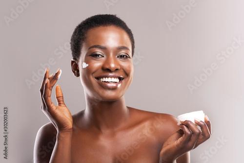 Fotografia Happy Afro Woman Holding and Applying Moisturizing Cream on Face