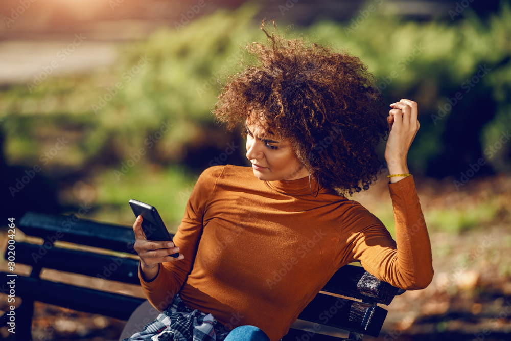Fototapeta Serious mixed race young woman with curly hair and in turtleneck sitting in park on bench and using smart phone for reading or writing message.