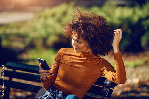 Fotografiet  Serious mixed race young woman with curly hair and in turtleneck sitting in park on bench and using smart phone for reading or writing message