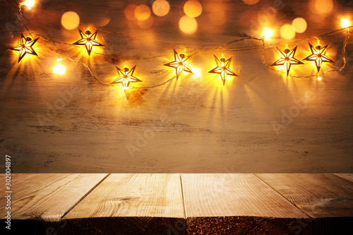 Obraz background image of wooden board table in front of Christmas warm gold garland lights. filtered. selective focus. glitter overlay - fototapety do salonu
