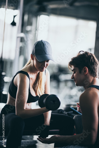 Fotografía  Athletic fitness woman pumping up muscles with dumbbells, Fit woman working out