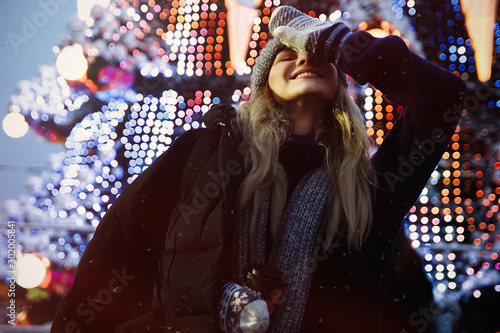 Valokuvatapetti photo with grain and aberrations under the old photo, film photo beautiful girl in a hat with coffee in the evening, basks, near the Christmas tree, winter holidays, holiday and walks