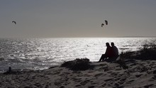 Human Silhouettes, Couple Sitting On Beach Sand Dune, Grass Blowing In Wind. Kite Surfer, Kitesurfing In Silver Mirror Glistening Sea Waters. Sun Reflection On Choppy Ocean Waves. African Beach Sunset