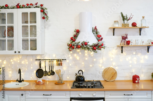 Fotografija  winter kitchen with red decorations, christmas cooking table and utensils