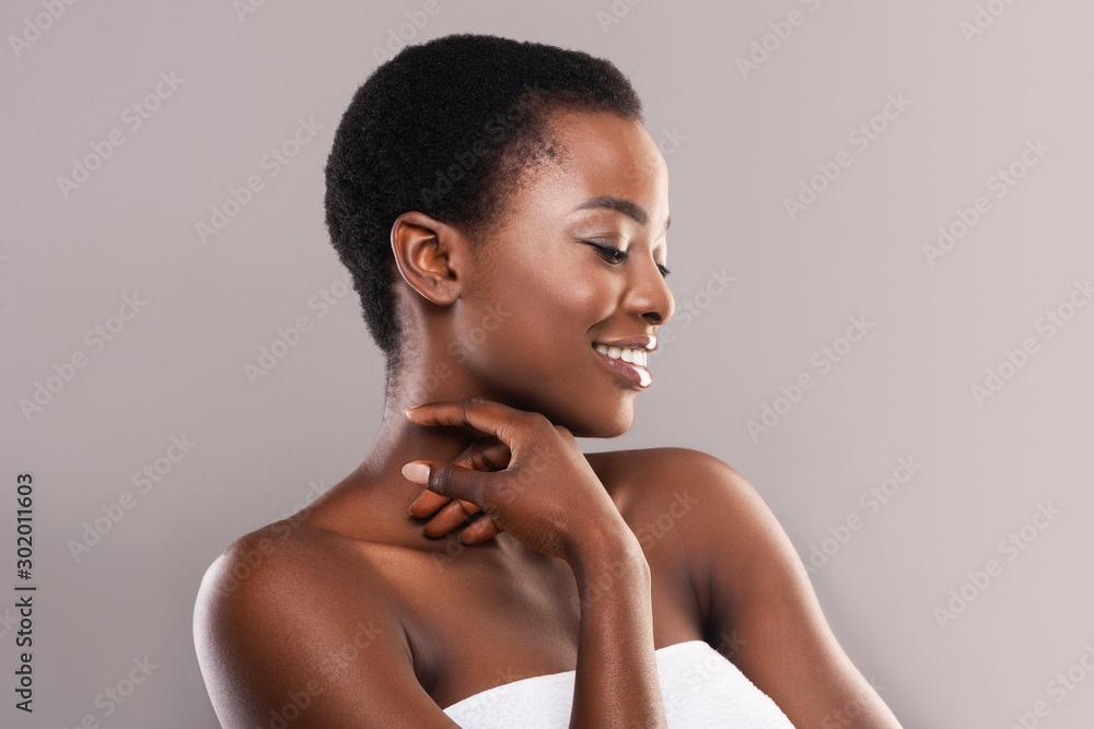 Fototapeta Beautiful black girl touching her velvet skin on neck