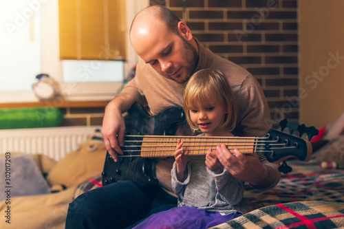 Cute little girl and her father are playing bass guitar and smiling while sitting on couch at home. Spending time together, learning to play the guitar - 302017203