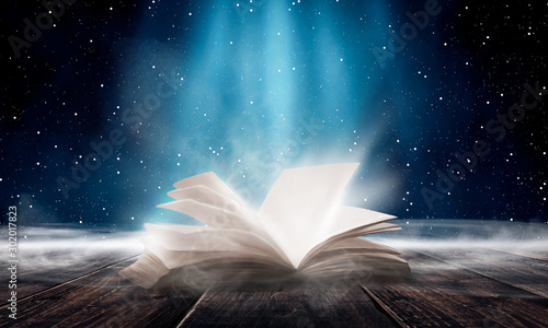 Obraz An open book on a wooden table under the night sky against a dark forest. Magical radiance. Night scene. - fototapety do salonu