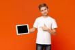 Leinwandbild Motiv Cool teenage boy pointing at blank screen of digital tablet