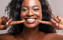 Happy Black Woman Pointing At Her Perfect White Teeth