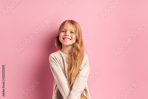 Obraz Portrait of positive cheerful girl cutely smiling at camera, girl with long golden hair in white blouse. Pink background - fototapety do salonu