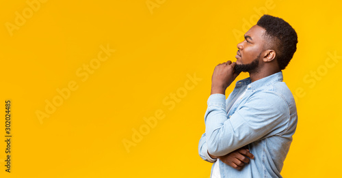 Cuadros en Lienzo Young african american guy thinking about something over yellow background