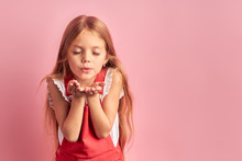 Portrait Of Little Caucasian Girl With Long Hair And Closed Eyes Sending, Blowing Kiss To Camera, Wearing Red Overalls Isolated Over Pink Background.