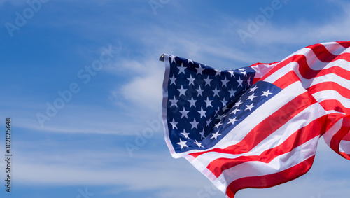 Obraz US American flag on blue sky background. For USA Memorial day, Veterans day, Labor day, or 4th of July celebration. Top view, copy space for text. - fototapety do salonu