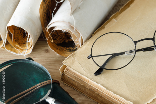 Fotomural  A book with old-fashioned glasses, a magnifying glass and rolled up old parchmen